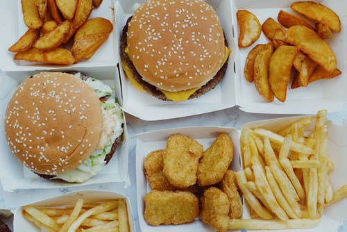 Top view of yummy junk food consisting of burgers and french fries with nuggets placed in boxes on marble background