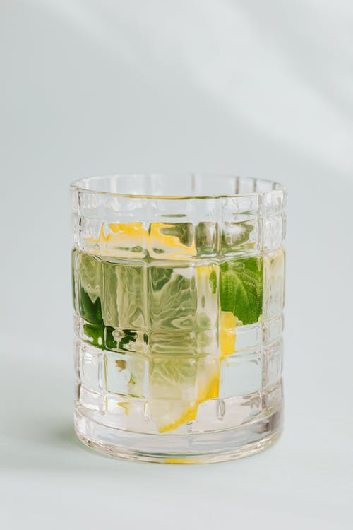 Glass of cold mojito on white background