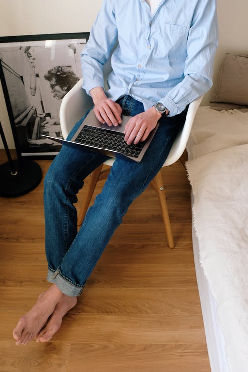 Unrecognizable man using laptop on chair