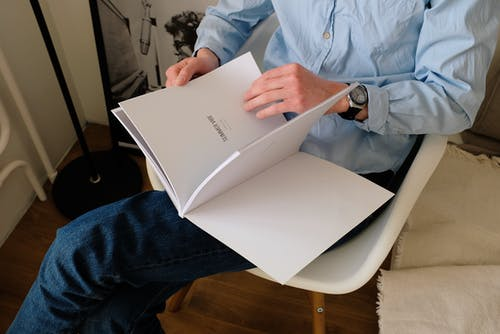 From above of faceless young man in casual wear sitting and crossing legs while reading book on chair in modern studio