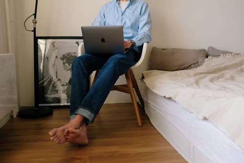 Faceless man working on laptop at home