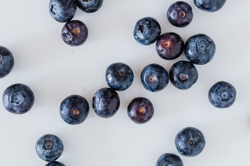 Top view of delicious ripe and sweet blueberry randomly scattered on white surface