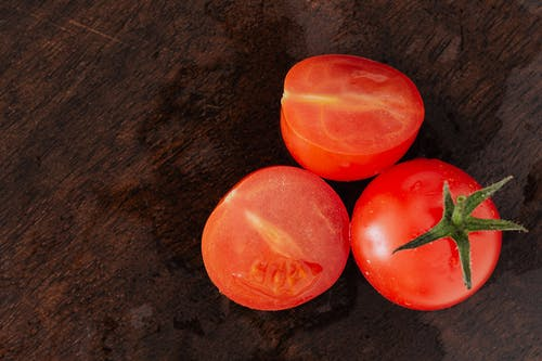 Bunch of ripe red tomatoes on wooden surface