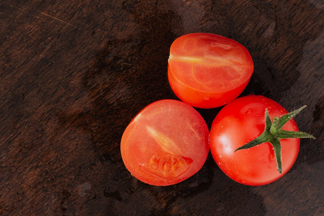 From above of delicious juicy cut in half of tomato placed with red whole tomato on dark brown table