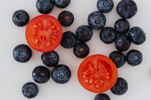 Halves of tomato and scattered blueberries