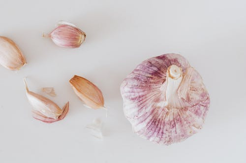 Garlic and cloves on white surface