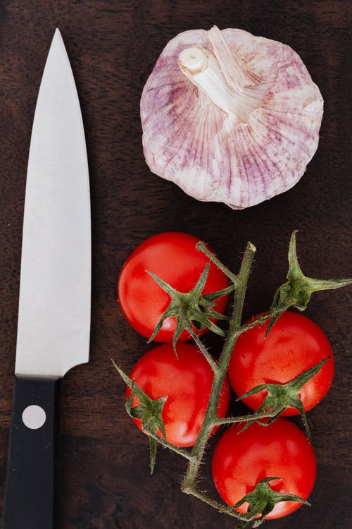 Tomatoes and garlic and knife on cutting board