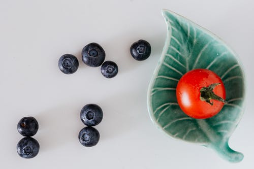 Minimalistic composition of fresh tomato on small designer platter near blueberries on gray background