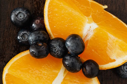 From above organic blueberries scattered on halves of ripe orange on lumber table prepared for raw breakfast