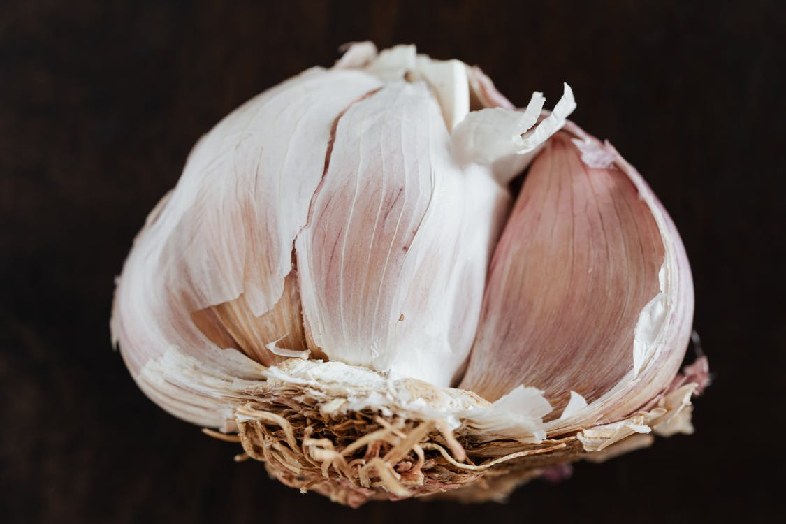 Top view of fresh halved garlic in peel placed on dark brown surface before training in restaurant