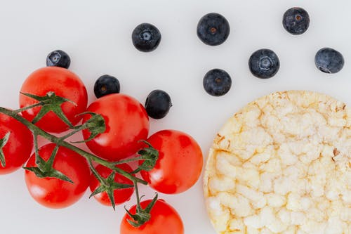 Rice bread near branch of delicious tomatoes and organic blueberries on gray table