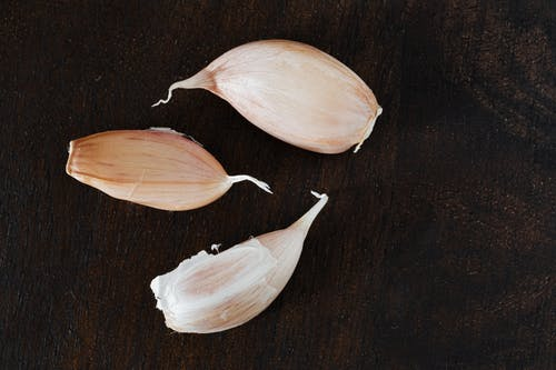 Top view of several cloves of ripe garlic in peel placed on wooden desk during cooking process at home