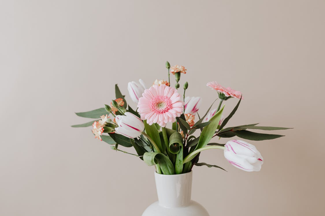 Light bouquet of fresh tulips with green leaves arranged with pink Gerberas and yellow red carnations in white ceramic vase