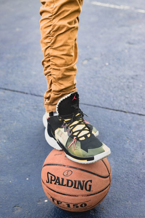 Crop unrecognizable male in trendy sneakers stepping on basketball ball while standing on sports ground