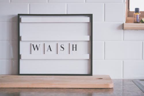 Signboard with word WASH in bathroom