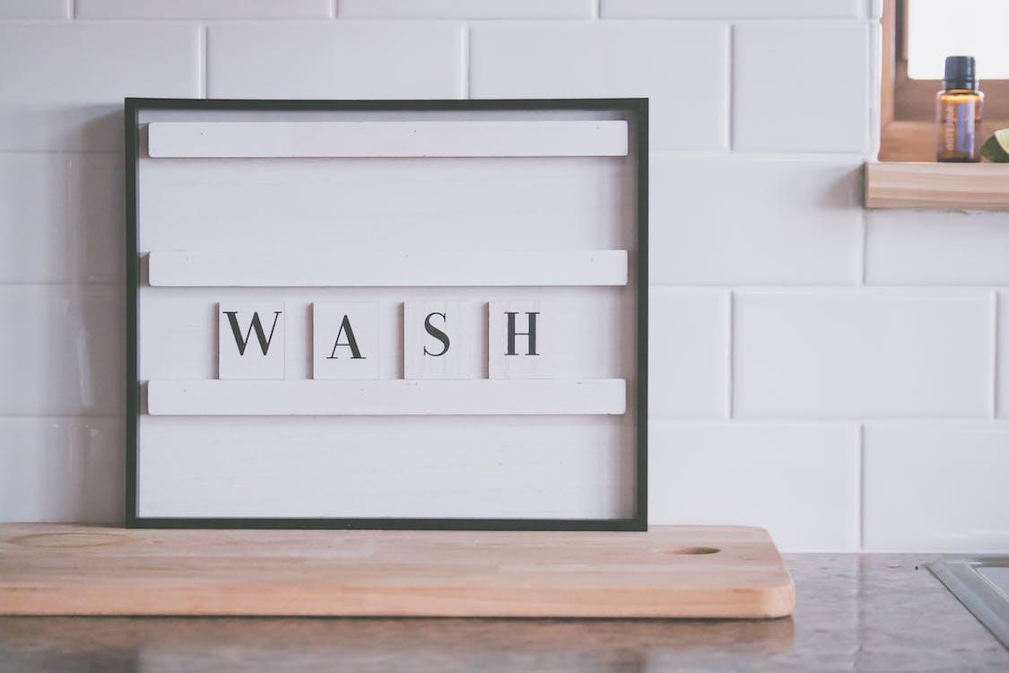 Signboard with word WASH in bathroom