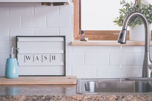 Board with word WASH placed near soap dispenser on counter in bathroom with water streaming from open faucet
