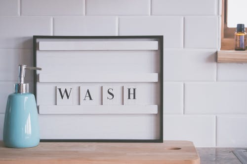 Board with word WASH placed near soap dispenser on counter in light bathroom representing concept of hygiene and coronavirus prevention