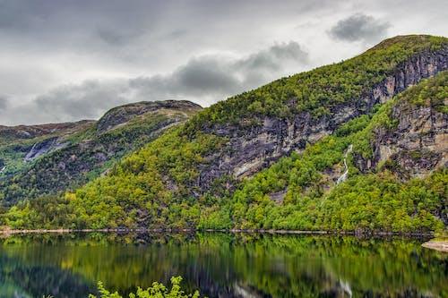 Mountain Beside Lake Under Cloudy Sky