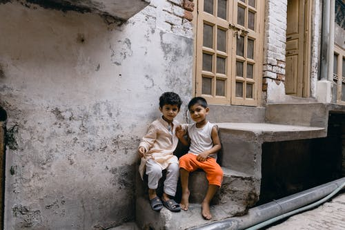 2 Boys Sitting on Concrete Stairs