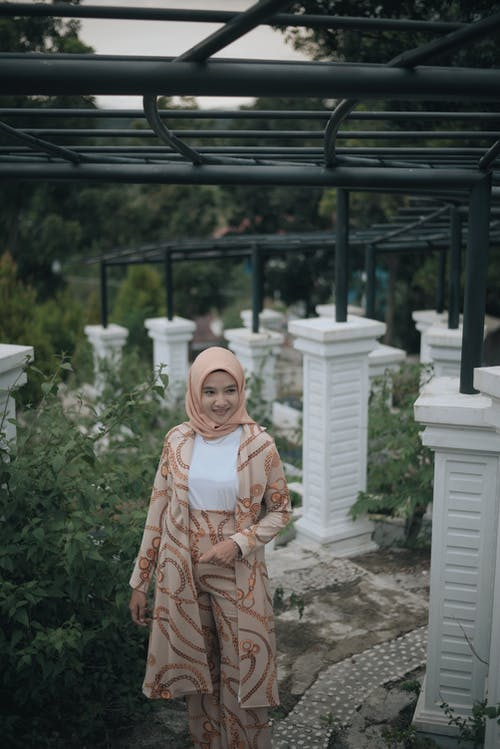 Young ethnic female in ornamental traditional garment and hijab walking along alley with columns in green garden