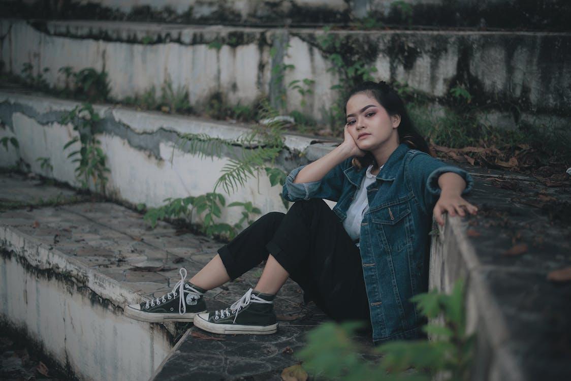 Ethnic teen girl sitting on stone steps on street