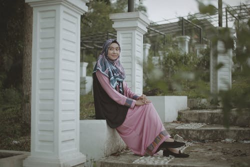 Full body side view of smiling young Asian female in traditional colorful dress and headscarf sitting on stone bench in park and looking away