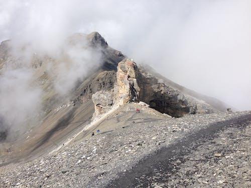 Breathtaking scenery of high rocky mountain peak hidden under gray clouds in wild valley