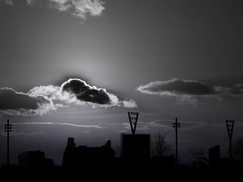 Silhouette of Buildings Under Cloudy Sky