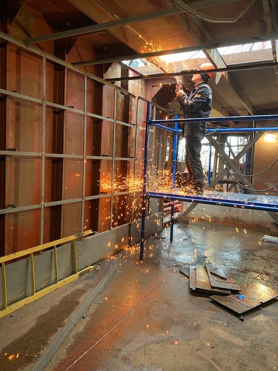 Welder working inside industrial building