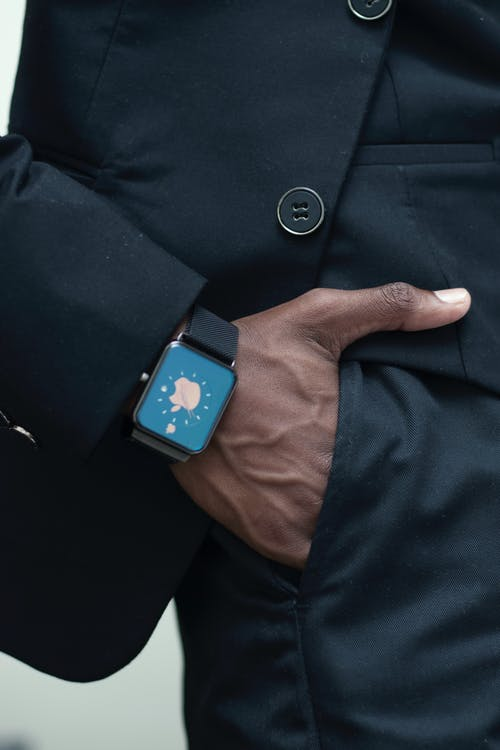 Crop unrecognizable black businessman in black formal suit with trendy smart watch holding hand in pocket