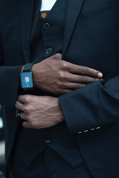 Anonymous person adjusting suit of unrecognizable African American gentleman in elegant outfit with modern smart watch
