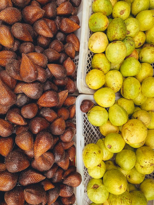 Top view of heap of ripe sala fruits with pointed edges and prickly surface near delicious yellow guava with smooth peel