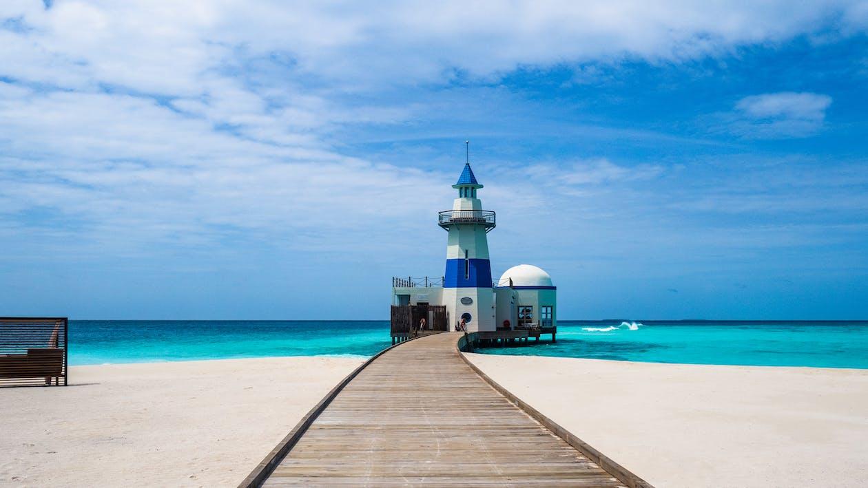 White And Blue Lighthouse Near Sea Under Blue Sky