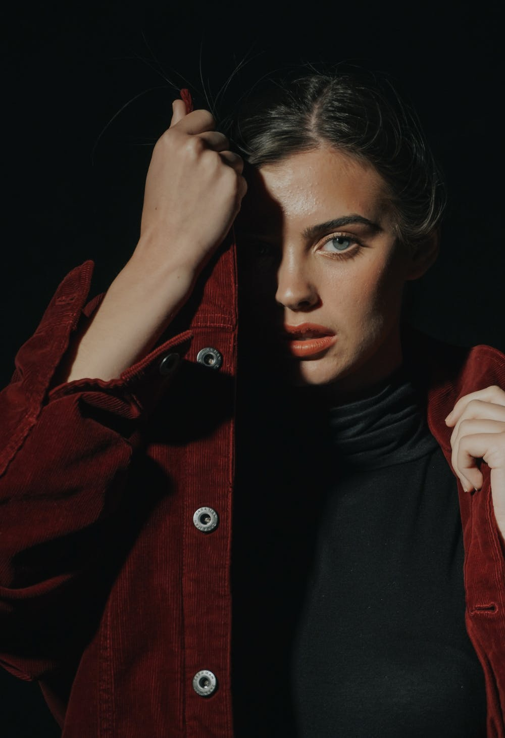 A woman wearing black shirt and red jacket. | Photo: Pexels