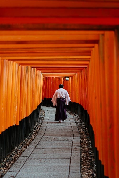 Woman in White Long Sleeve Shirt and Black Pants Walking on Orange Tunnel