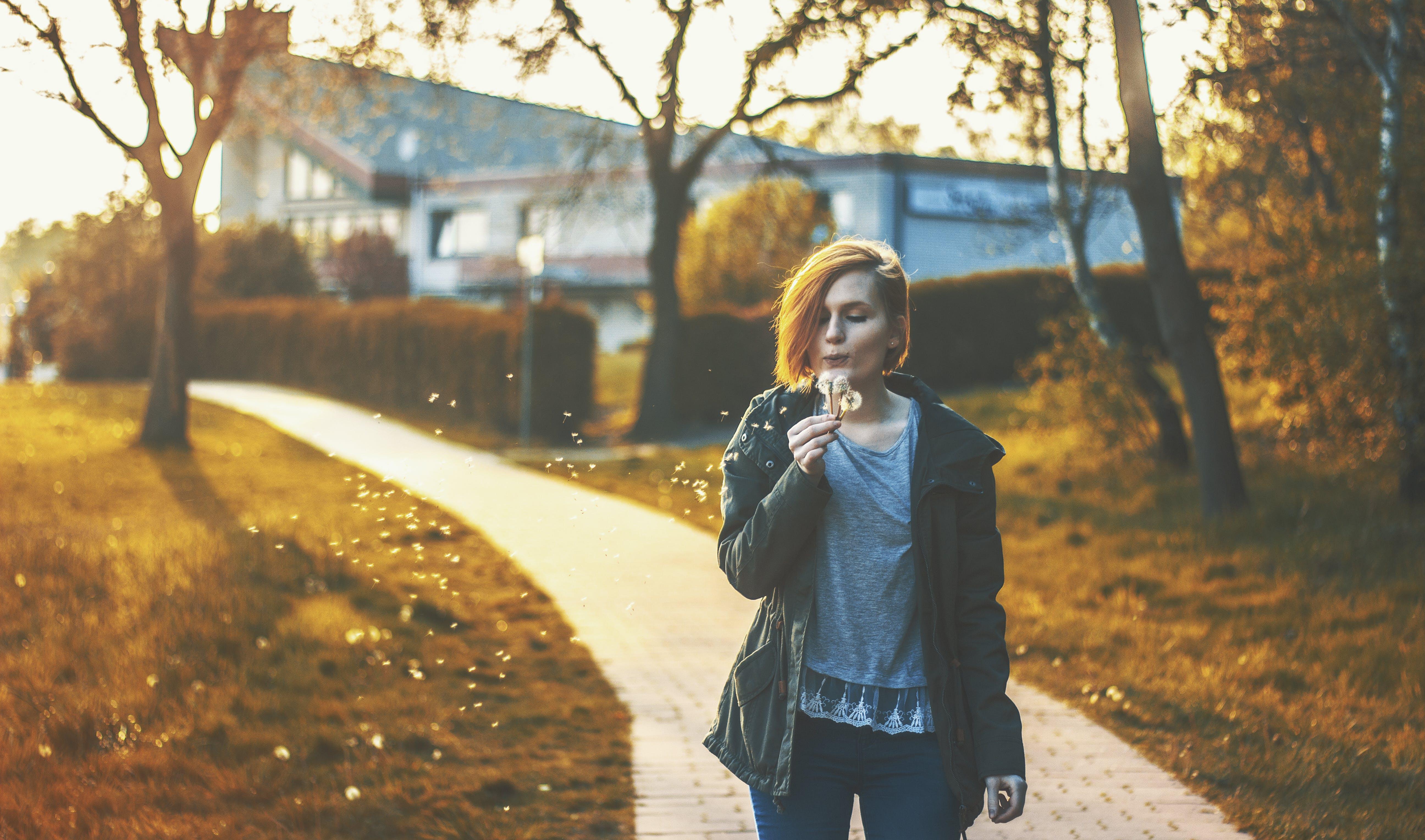 Woman Blowing Dandelion Flower Standing on Pathway