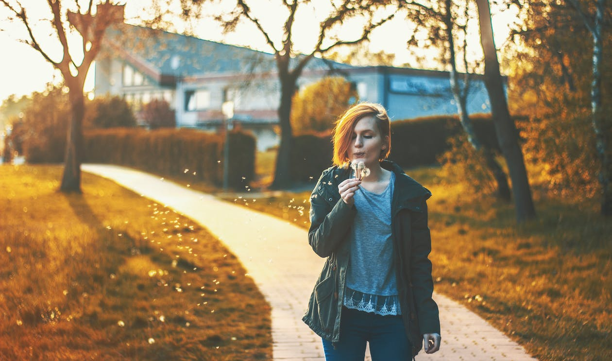 Woman Blowing Dandelion Flower Standing on Pathway