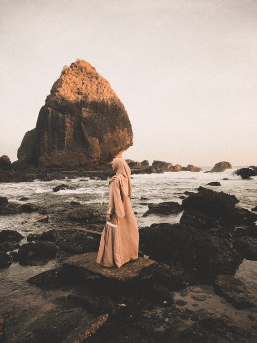 Woman Standing On Rocky Shore