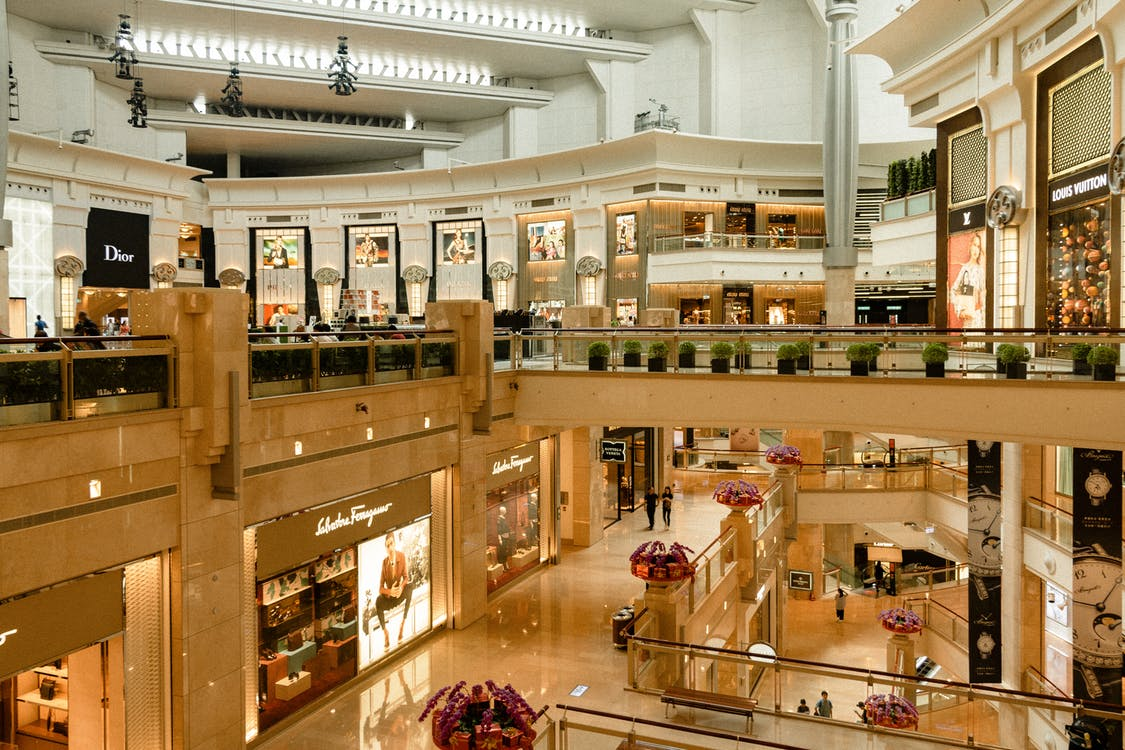 Contemporary design of big mall interior with ribbed column and decorative elements on ceiling with glowing corridors illuminated by artificial lights and signboards with inscriptions