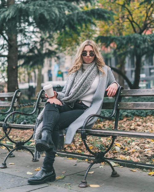 Woman In Gray Coat Sitting On Black Metal Bench