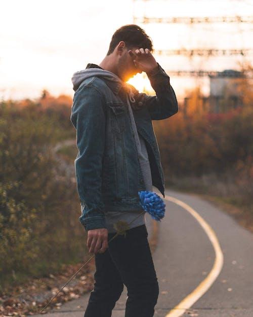 Man In Blue Denim Jacket Holding Blue Flower