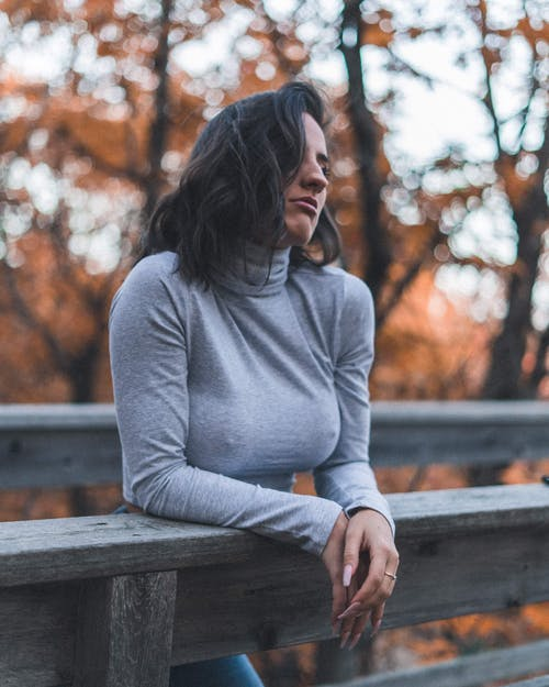 Woman iI Gray Long Sleeve Shirt Leaning On Wooden Fence