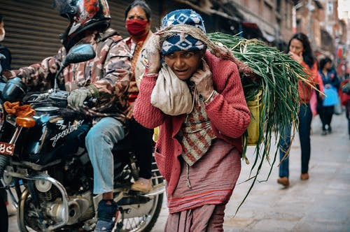 Mature ethnic female in national clothes carrying bunch of green herbs tied with rope while strolling on concrete pavement near couple on motorbike and houses in town and looking away