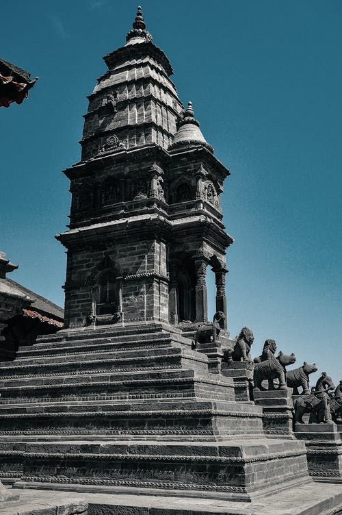 From below of aged masonry church facade with stairs and statues of animals under cloudless sky in daylight in Bhaktapur