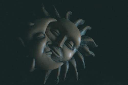 Visual artwork of tender moon and sun clay faces