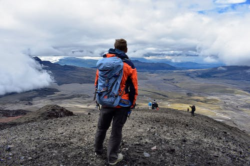 Man in Orange Jacket and Blue Denim Jeans Standing on Rocky Ground Looking at Mountains during