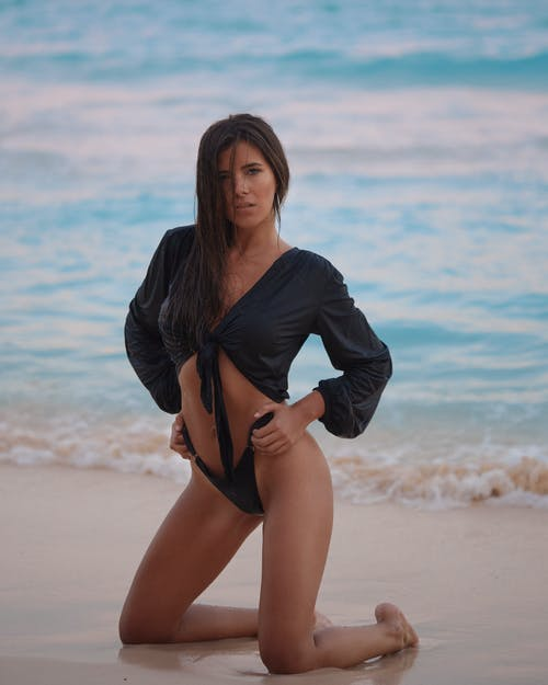 Woman in Black Long Sleeve Shirt and Black Panty Standing on Beach Shore