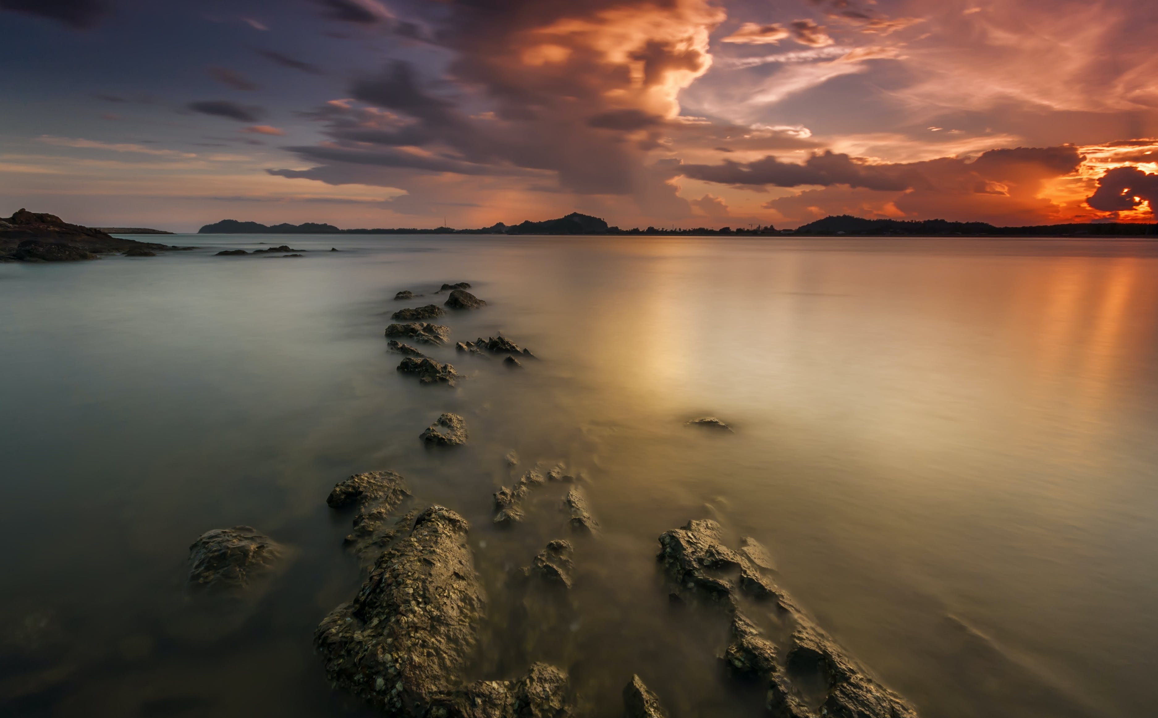 Time Lapse Photography of Body of Water and Sunset