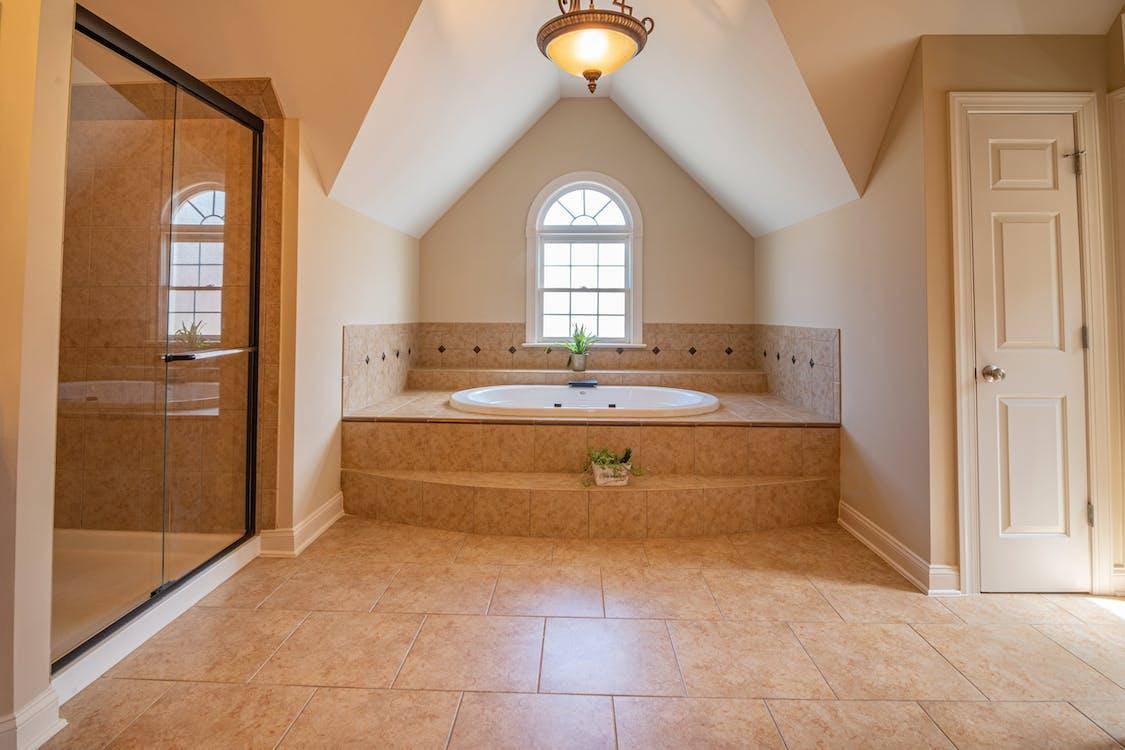 White Bathtub Near Brown Wooden Door